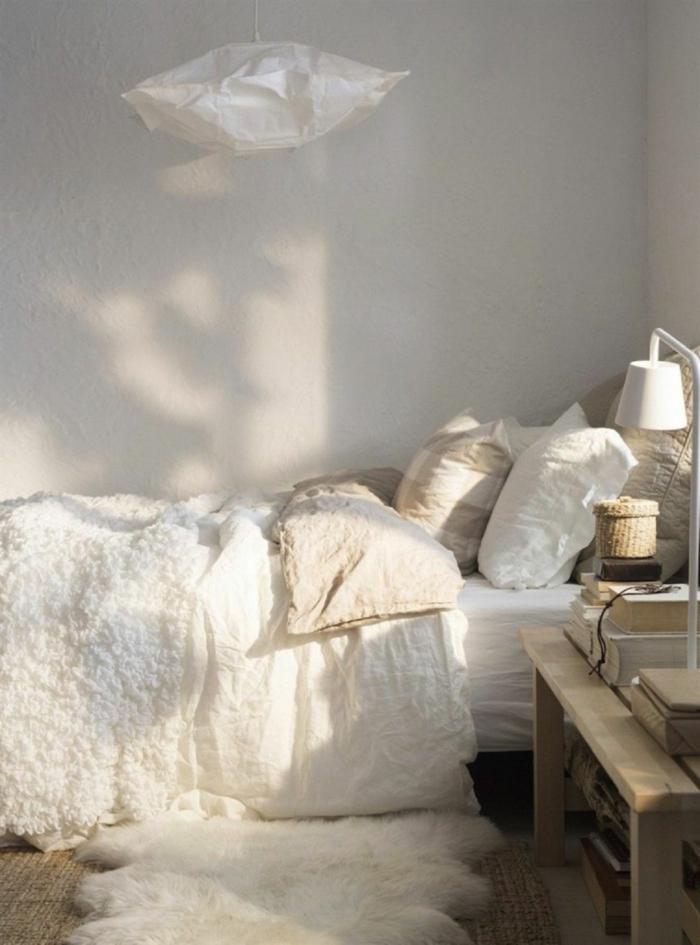 fourrure blanche sur un lit, suspension en papier, coussins blancs, petit panier tressé, lampe de table blanche