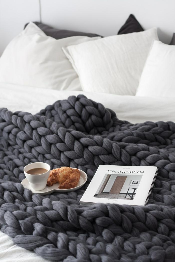 décorer sa chambre scandinave, plaid tricot gris anthracite, tasse de café et croissant, coussins blancs
