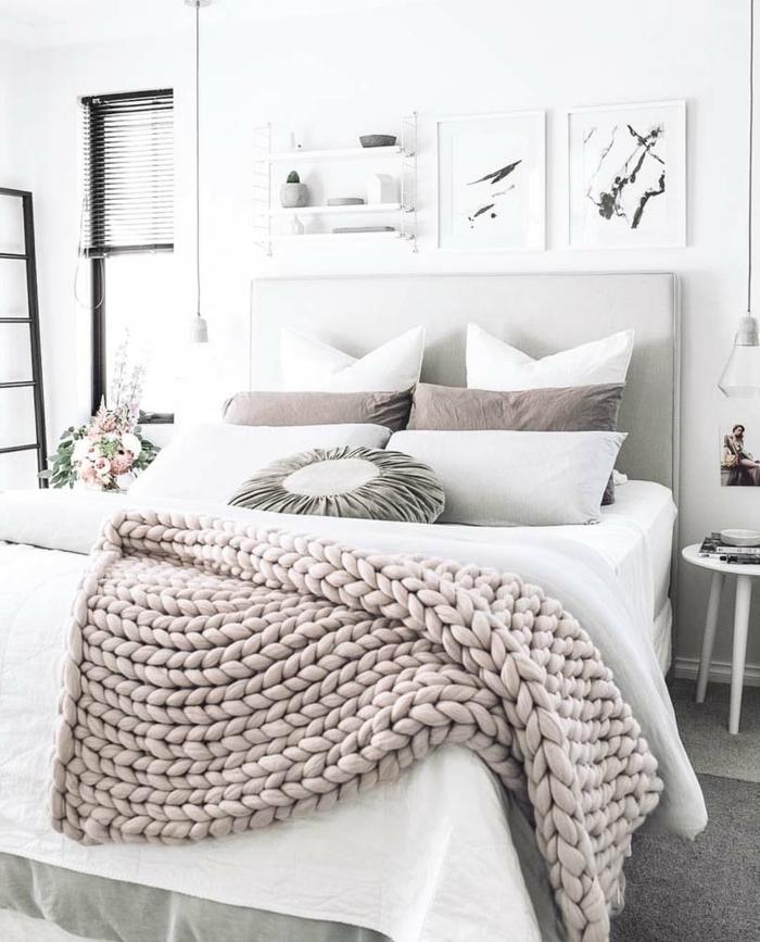 lit déco scandinave, plaid tricoté rose nude, coussins, tableaux peintures, petit tabouret blanc