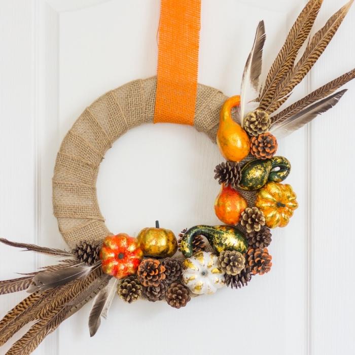 modèle de couronne décorative fait main avec plumes citrouilles et pommes de pins colorées, idée que peut on faire avec des pommes de pin