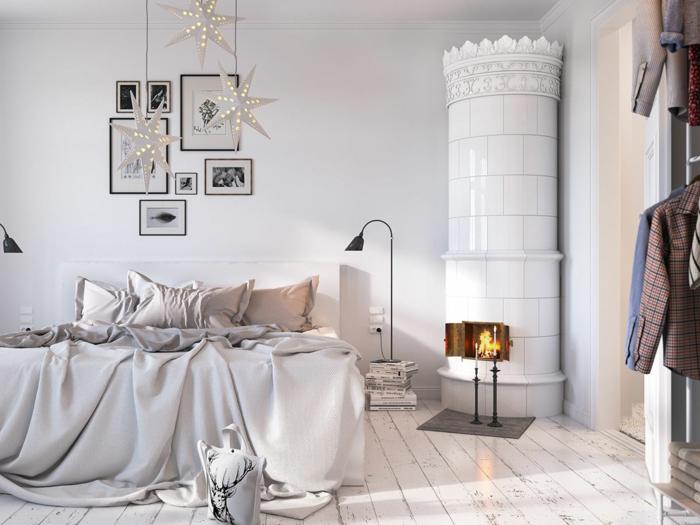 sol en planches de bois, lit couvert de jetés moelleux, sol en planches blanches, poêle scandinave, cadres peintures