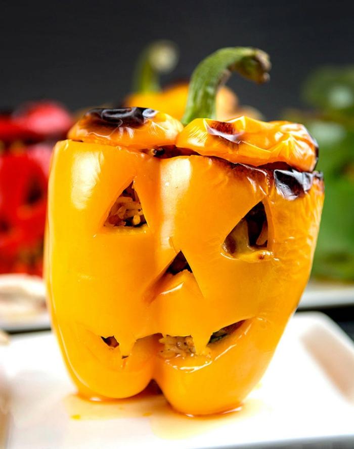 des poivrons farcis d'halloween découpés comme des citrouilles effrayantes lanternes d'halloween à servir comme plat principal