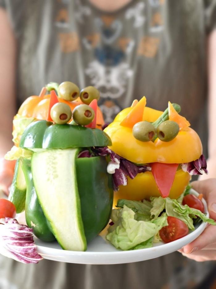 recette santé pour le repas halloween, des poivrons farcis de salade verte en forme de monstres d'halloween