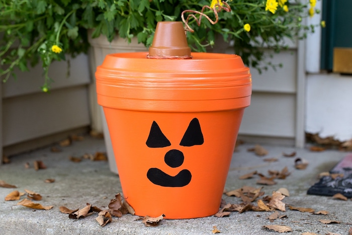 jack o lantern motif citrouille sur un pot en terre cuite avec couvercle orange et dessin à l indélébile noir sur pot