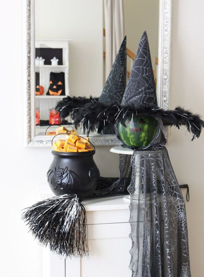 pot à feu noir et un pastèque transformé en sorcière avec chapeau sorcière et une cape sorcière, deco halloween maison