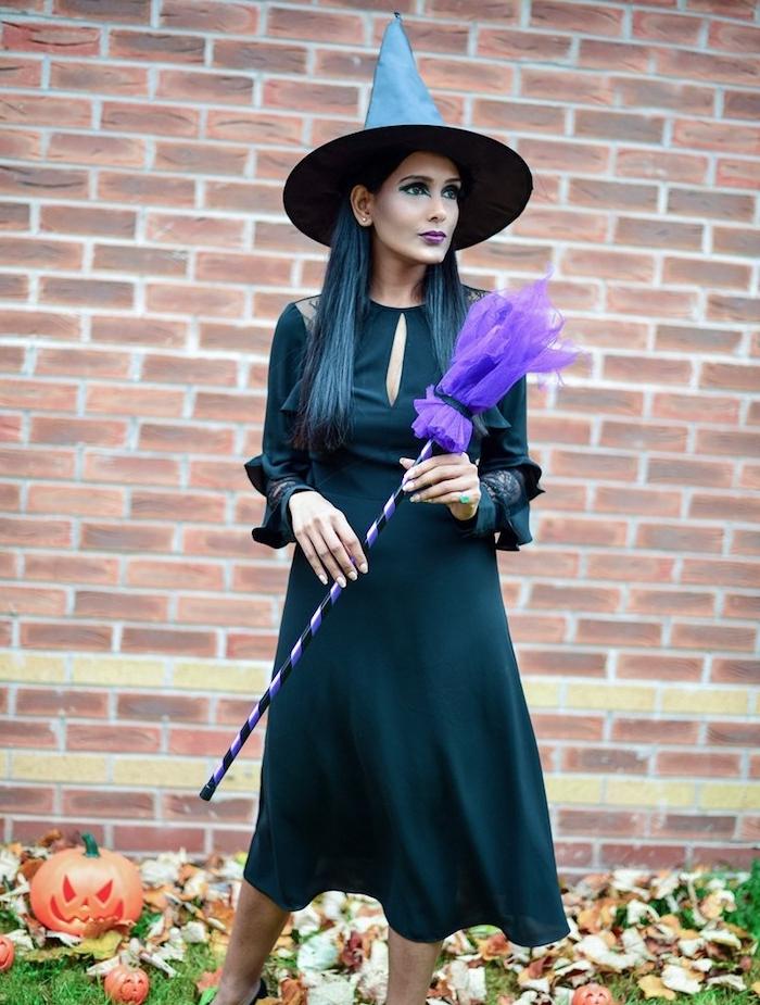 tenue sorcière en robe noire longue avec manches, chapeau de sorciere classique, balai magique en tulle, maqulillage foncé dramatique avec des ombres yeux foncés