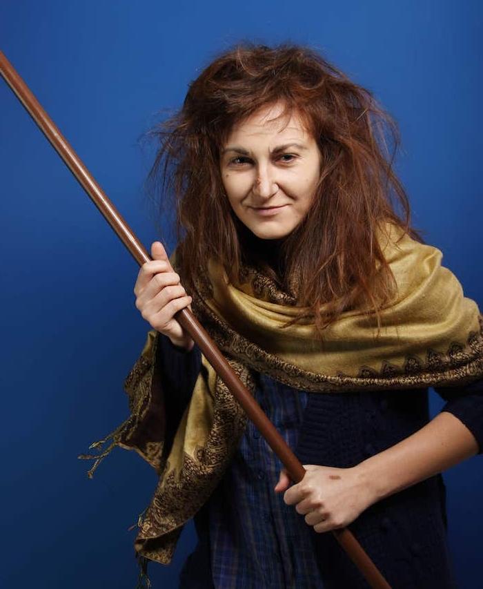 deguisement de sorciere traditionnel, femme aux cheveux ébouriffés, look sans maquillage, écharpe vert olive et chemise bleue, balai dans les mains