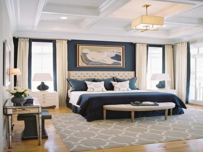 tapis gris géométrique, mur bleu derrière la tête de lit, banquette de lit en bois, commode argentée