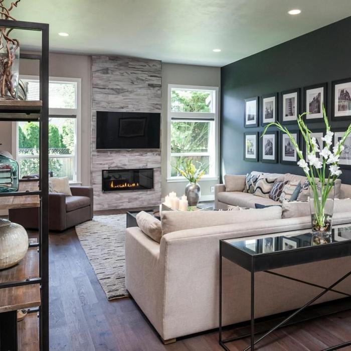 salon spacieux, cheminée murale montée, deux fenêtres, grands sofas crème, table noire plateau miroir, étagère bois et fer