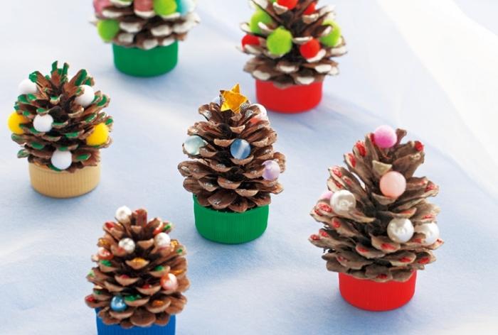 modèle de sapin en pomme de pin, activité manuelle maternelle pour noel, exemple de petit sapin diy décoré avec pompons