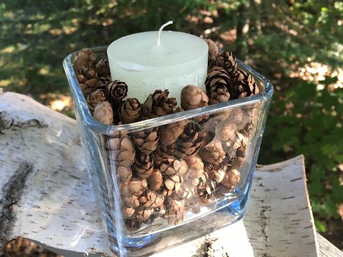 réaliser un porte-bougie facile dans un récipient en verre rempli de pommes de pin, idée que peut on faire avec des pommes de pin
