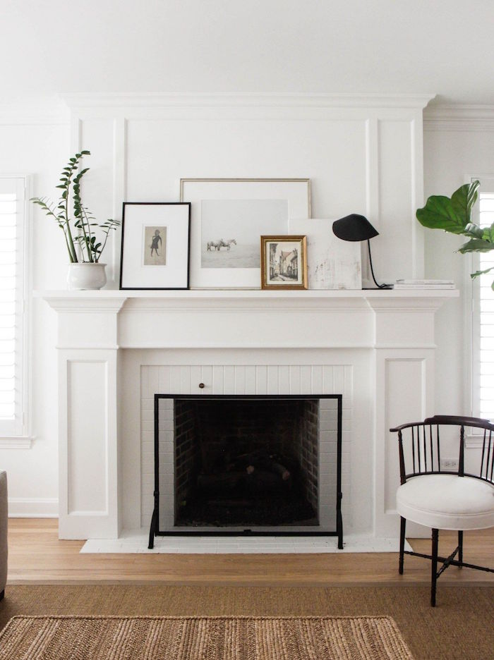 cheminée blanche avec design simple et classique, cadres décoratifs sur mur blanc