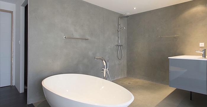 revêtement béton ciré sur sol et murs de salle de bain avec baignoire ilot ovale sans carrelage