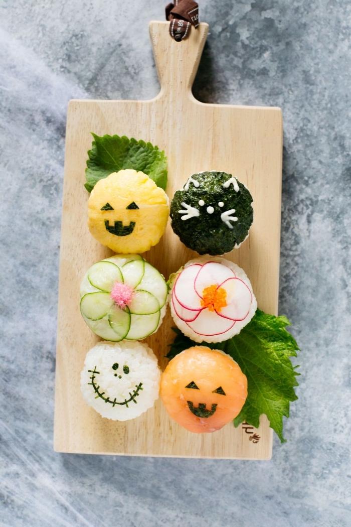 recette de temari sushi décoré pour la table d'halloween, boules de riz recouvertes de morceaux de saymon, algues, radis et concombre