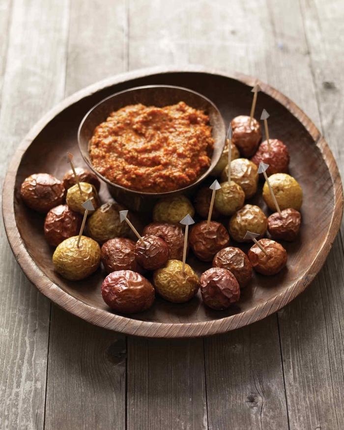 des pommes de terre nouvelles cuites au four, décorées avec des cure-dents façon queues de diable, servies avec de la sauce romesco