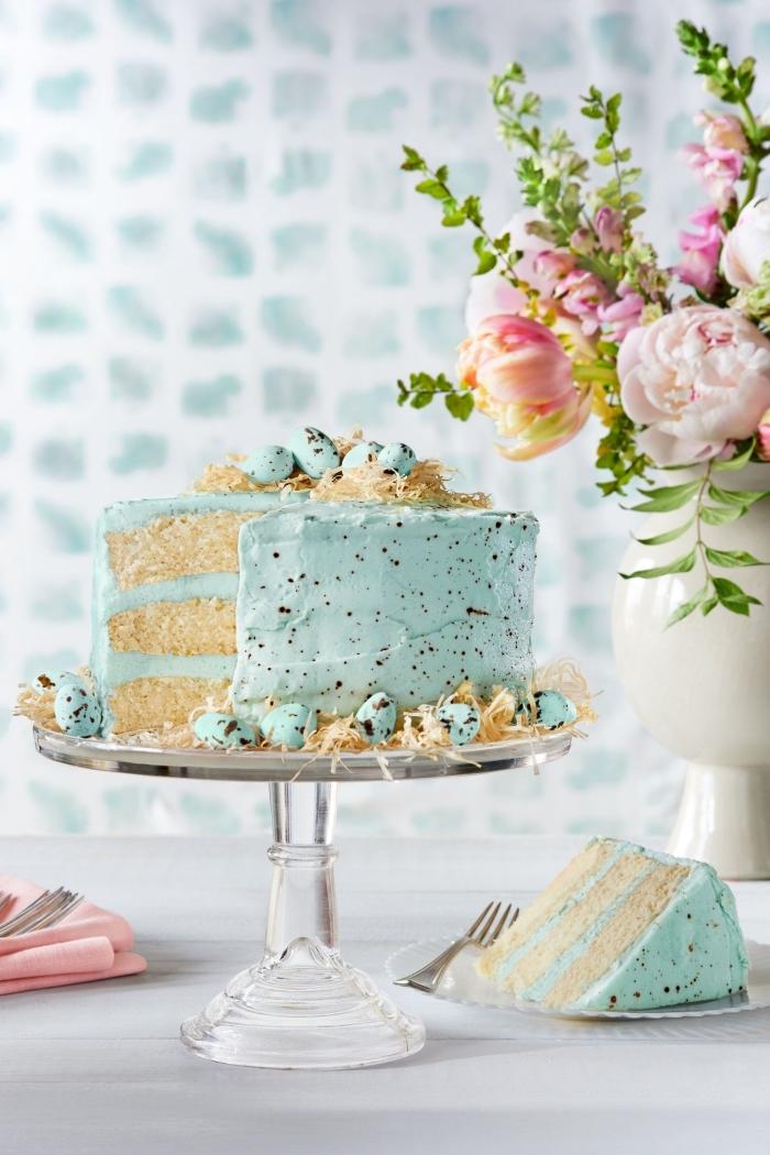 idée originale pour un gâteau de pâques vanille et noix de coco, recouvert d'un nappage gateau coloré bleu pastel et décoré avec des oeufs au chocolat