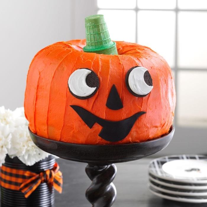 modèle de gâteau en forme de citrouille au glaçage orange avec décoration en cookies et fondant à design visage effrayant