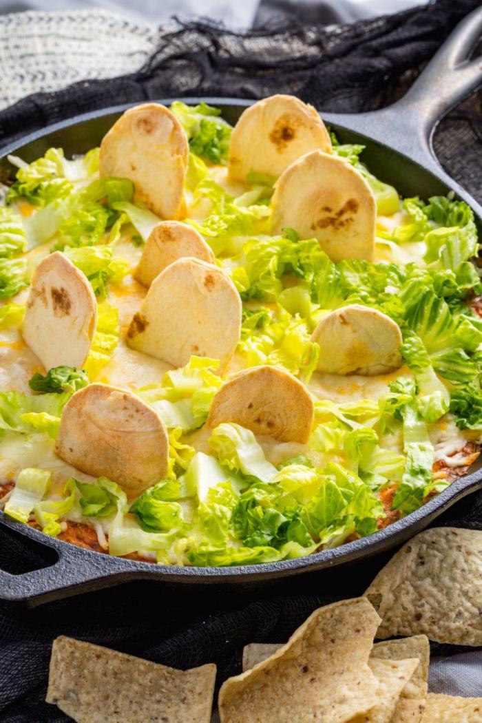 recette de nachos mexicaine servi en poêle décoré avec des morceaux de tortilla façon cimetière, parfaite pour un apéritif halloween effrayant