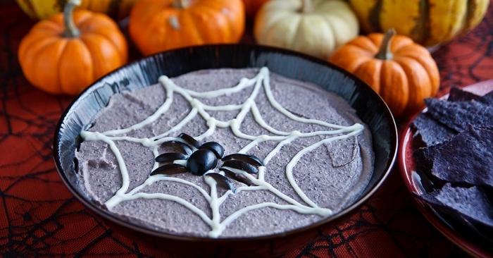 recette de houmus aux haricots noirs décoré façon une toile d'araignée avec une araignée en olives noires