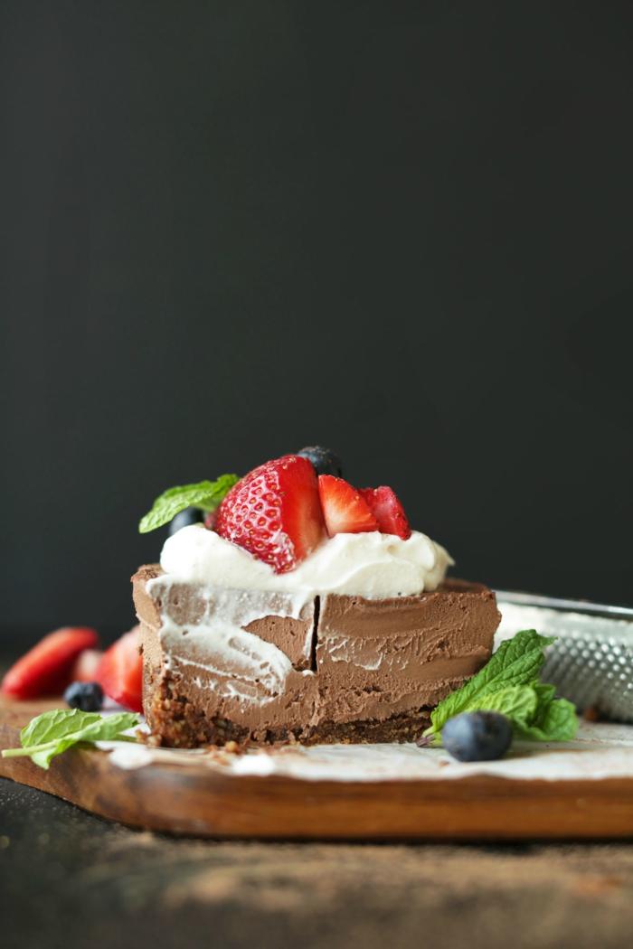 recette de dessert vegan, cheesecake cru sans cuisson au chocolat avec une base de dattes, noix et cacao garni de crème de noix