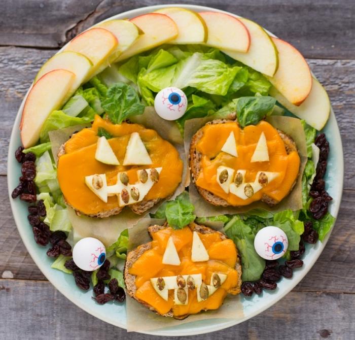 recettes healthy pour un apéro d'halloween, des tartines effrayantes au fromage en forme de citrouille d'halloween jack o'lanterne servies avec des feuilles de salade et des tranches de pomme