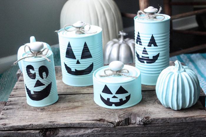 recyclage boites de conserve repeintes en bleu avec un motif jack o lantern en peinture noire avec des tiges en boutons de porte et ficelle, décoration halloween maison hantée