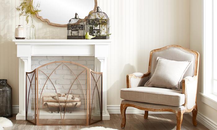 fausse cheminée décorative à cadre blanc et fond en briques banches et buches en déco, fauteuil en bois vintage, cages à oiseaux rétro