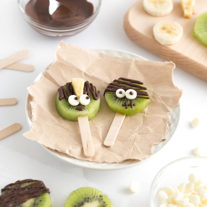 des sucettes de kiwi au chocolat à grignoter pour un apéro d'halloween santé, des amuse-bouches originaux et rigolos pour les enfants