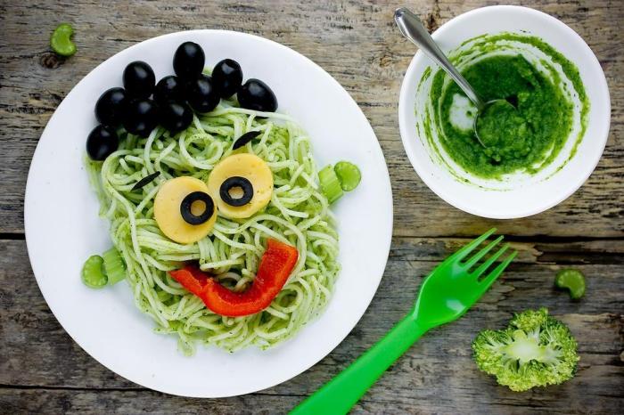 recette d'halloween facile pour régaler les enfants, des pâtes frankenstein au pesto vert, décorées avec des légumes et des olives