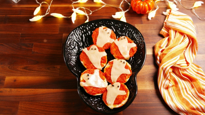 des mini-pizzas apéritives tomate et mozzarelle en forme de fantômes d'halloween, recette facile pour un apero dinatoire halloween à la fois effrayant et savoureux