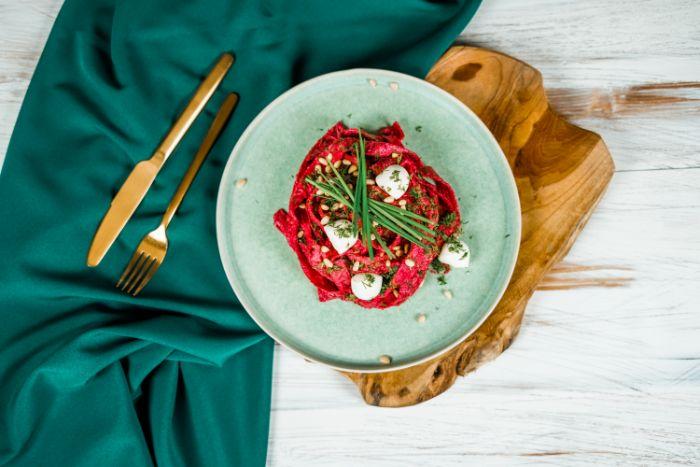 repas elegant pâtes à la betterave avec petites boules de mozzarella dans assiette bleu ciel idee repas pour halloween original