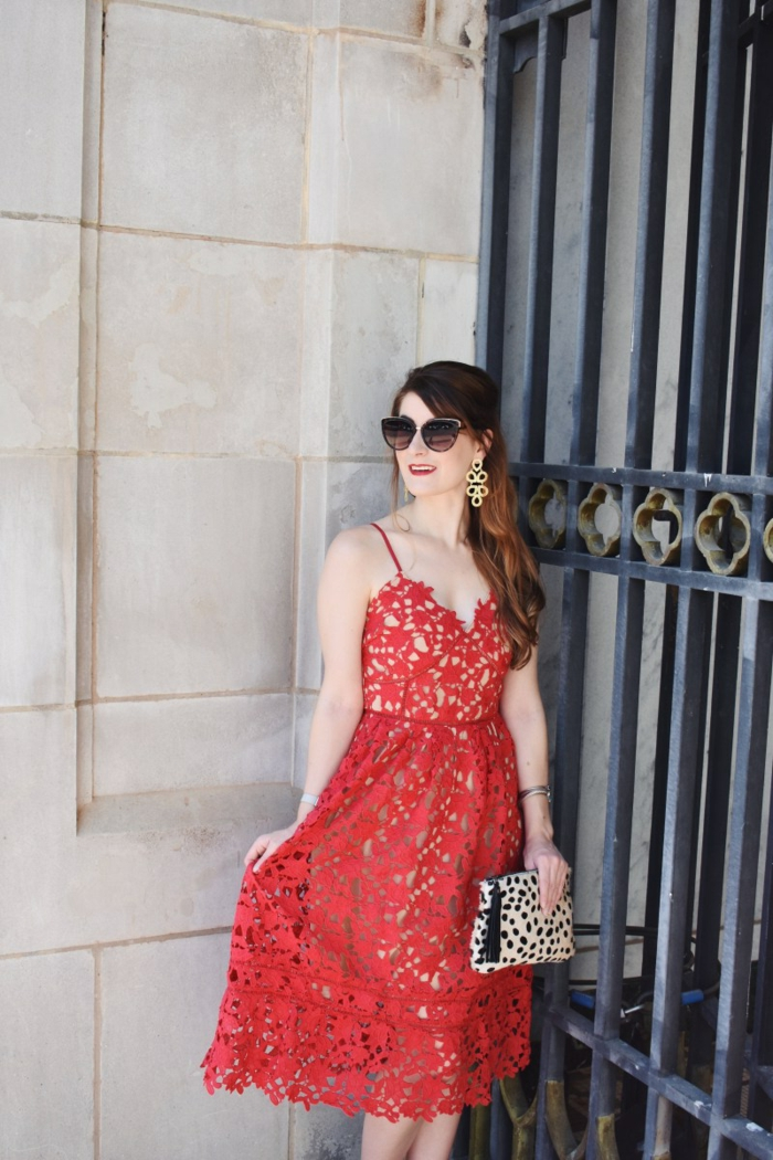 invitée de mariage près d'un grand portillon en fer, lunettes de soleil, sac tendance aux imprimés animaux