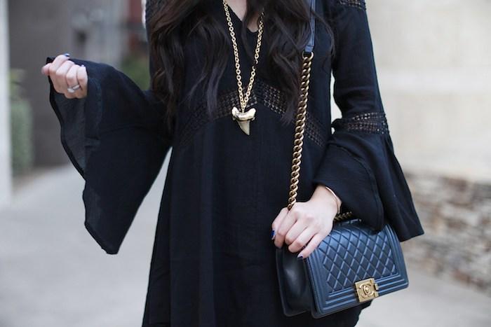 idée de look déguisement sorcière femme, robe noire avec des manches longues évasées, sac à main noir, collier or sorcière