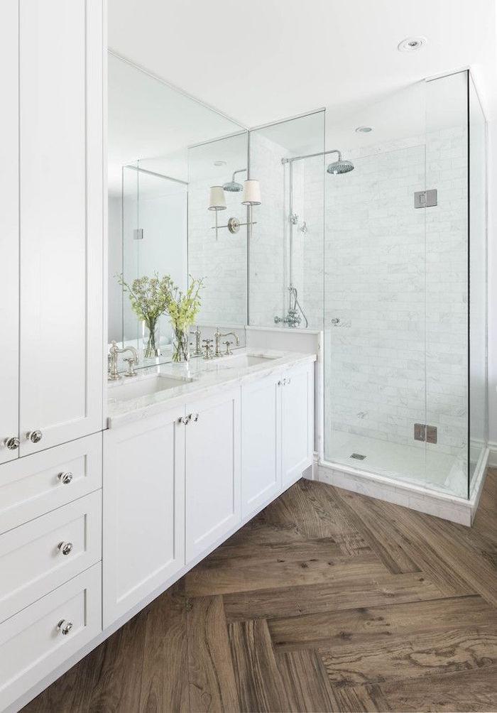 salle de bain blanche avec douche italienne à paroi transparente et sol en parquet bois