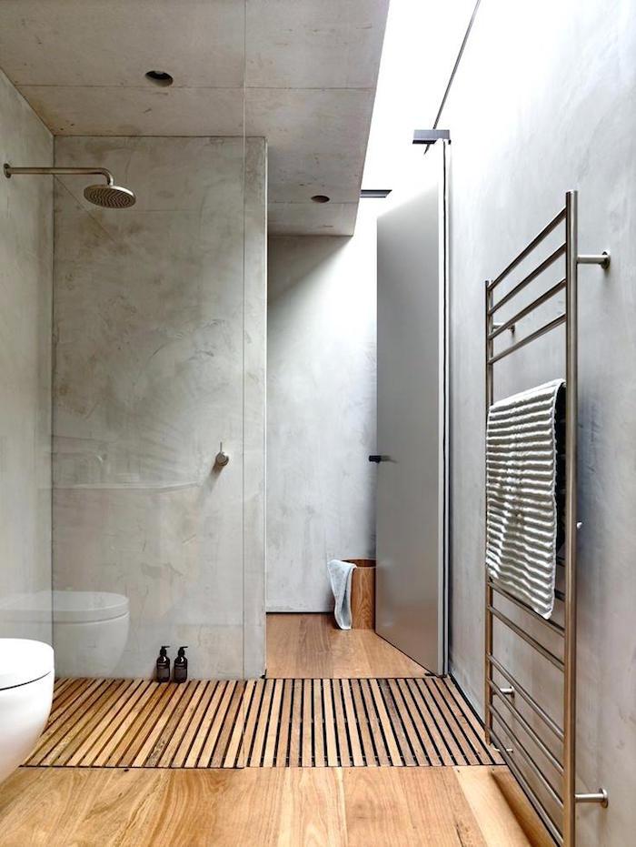 sans de bain moderne en béton ciré avec douche italienne sur sol en bois parquet