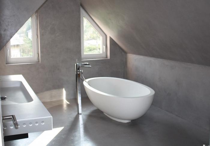 salle de bain mansardée dans combles recouverte de béton avec baignoire ilot ovale