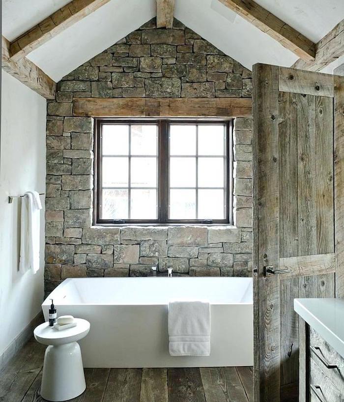 salle de bain ancienne rénovée avec pierres grises anciennes, sol en parquet et porte en bois vintage