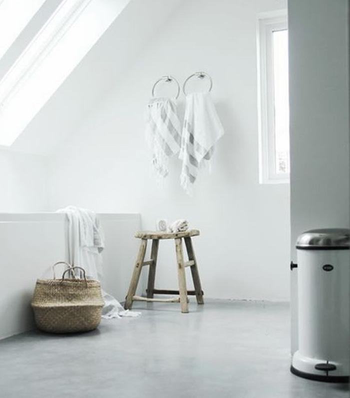 salle de bain mansardée blanche avec baignoire et sol en béton ciré gris sans carrelage, tabouret en bois vintage