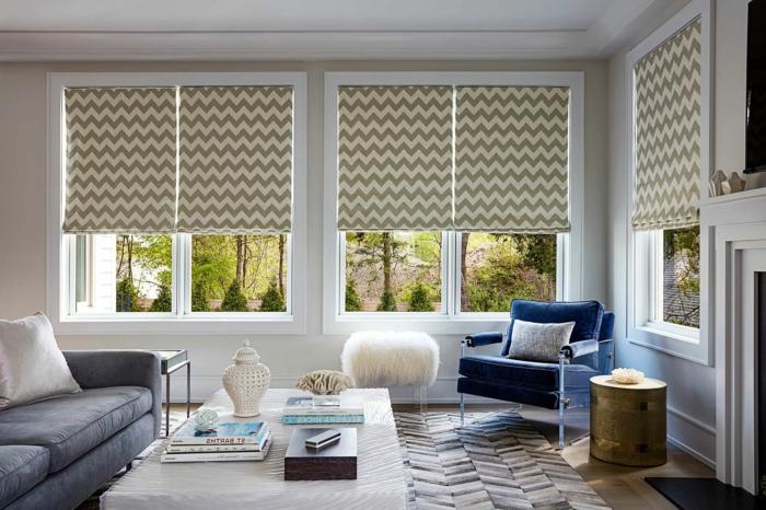salon aux couleurs claires, table rectangulaire, sofa gris, grande chaise bleue, petite table ovale dorée, store d'intérieur à motifs graphiques