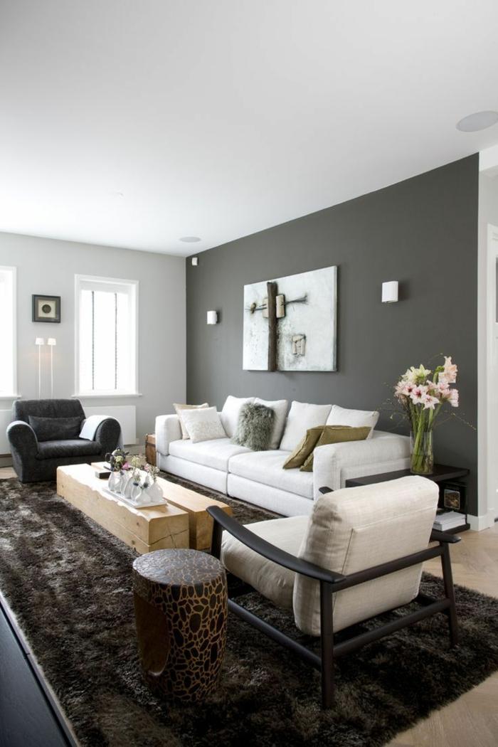 peinrure mur foncé dans un salon contemporain, tapis taupe, table basse bois brut, tabouret ethnique