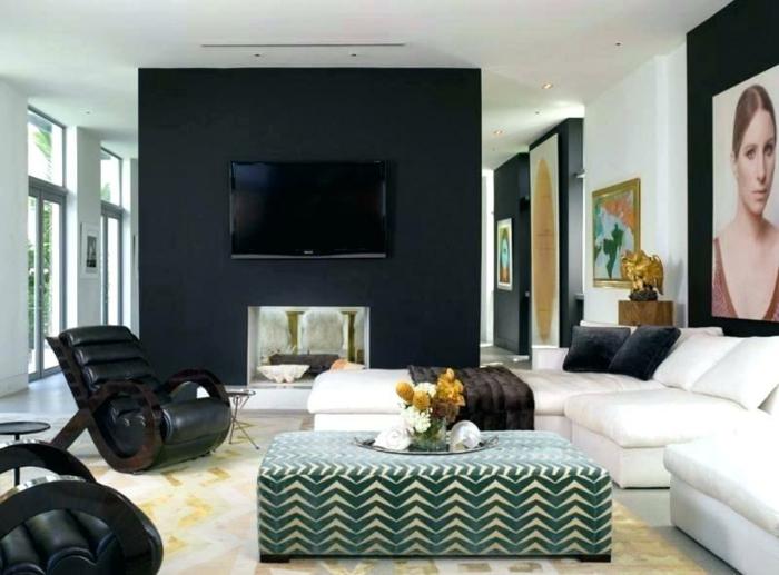 décorer un grand pan de mur avec photographies et peintures, mur noir, fauteuils en cuir cosy, tv murale