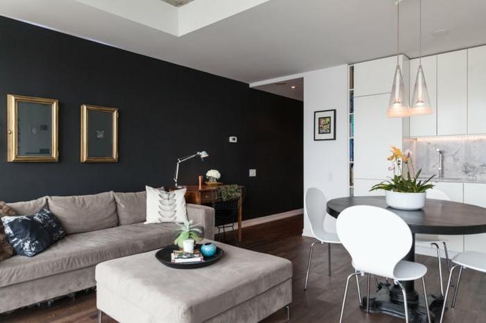 salon en gris blanc et noir, tabouret gris, sofa gris, salon et cuisine table noire ovale, chaises blanches, quel mur peindre en couleur