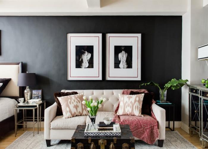 tableaux avec photographies, sofa beige, table valise vintage, tapis gris, mur noir dans le salon