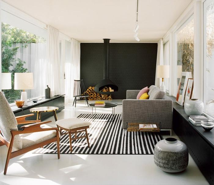 salon moderne aux traits rustiques, decoration salon peinture noire, meubles scandinaves, sofa gris épuré, cheminée suspendue, tapis rayé, fenêtres du sol au plafond
