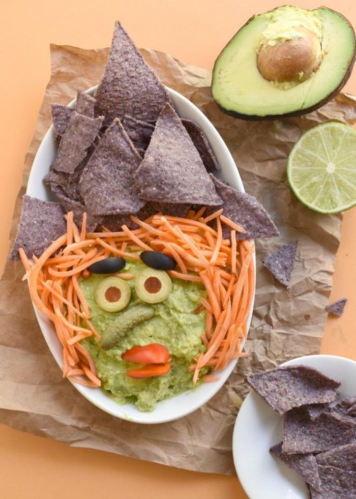 guacamole pour l'apéritif d'halloween en forme de tête de sorcière décoré avec chips tortilla de sarrasin, olives, carottes râpées et mini-cornichon