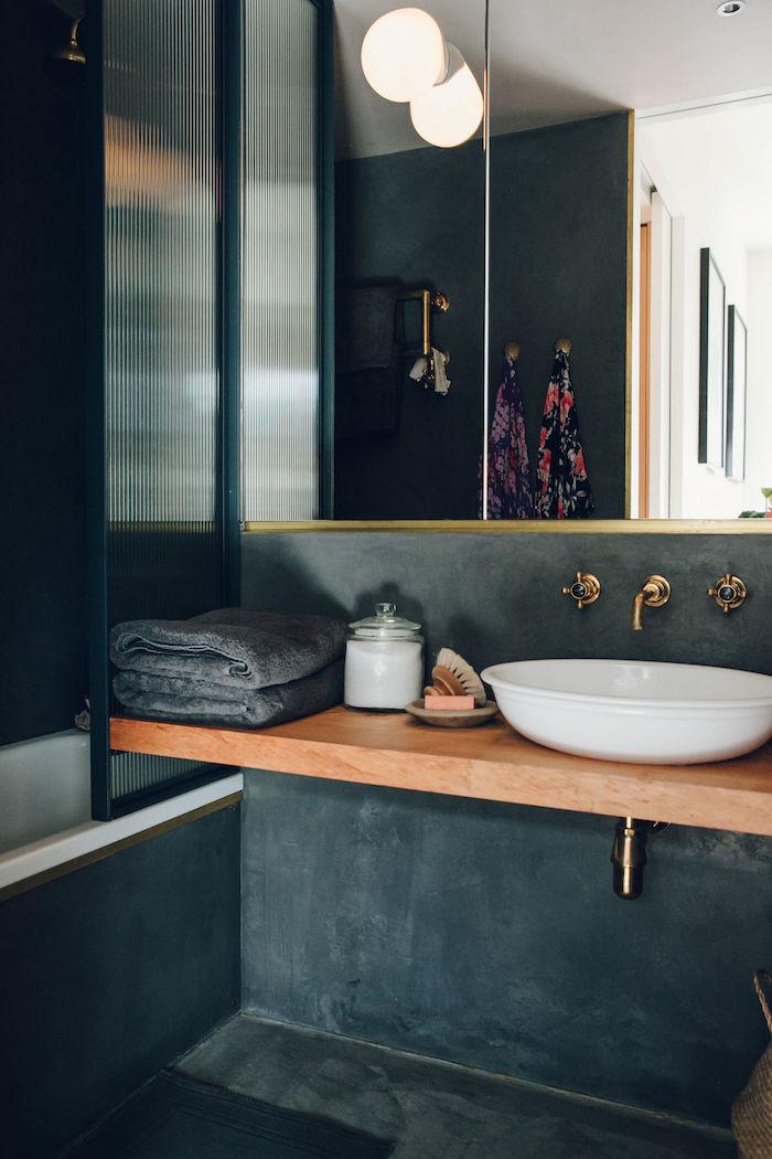 salle de bain en TADELAKT gris foncé avec baignoire et support lavabo vasque en bois