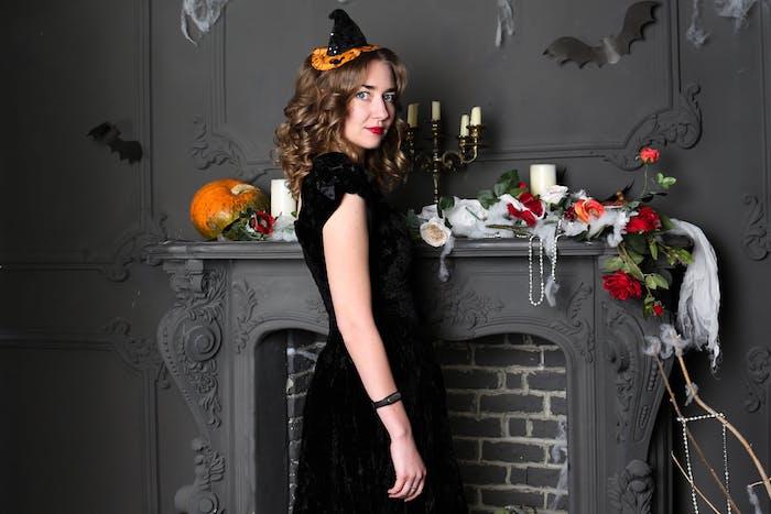 deguisement magicien, style sorcière avec une robe noire et un chapeau sorcière original en noi et orange, deco cheminée halloween