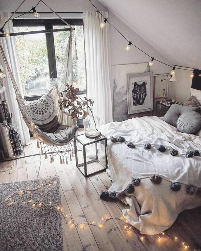 cadre peintures loup, guirlande d'ampoules, plancher en bois, grande fenêtre, chaise suspendue, parure de lit pompons gris