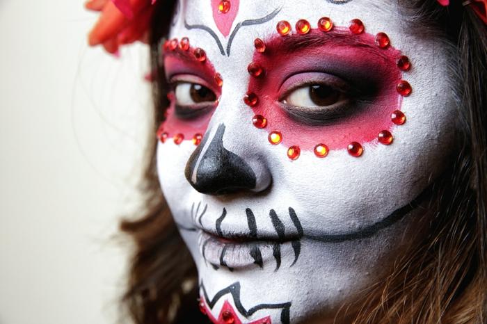 maquillage halloween mexicain, pailettes oranges autour des cercles rouges, nez noir, fleur au menton