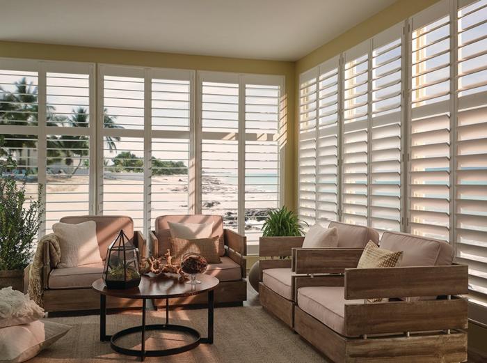 canapé confortables, table ronde, coussin de sol beige, tapis couleur sable, stores d'intérieur et baies vitrées